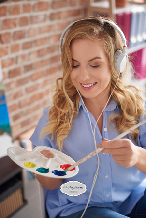 Woman relaxing while painting pictures